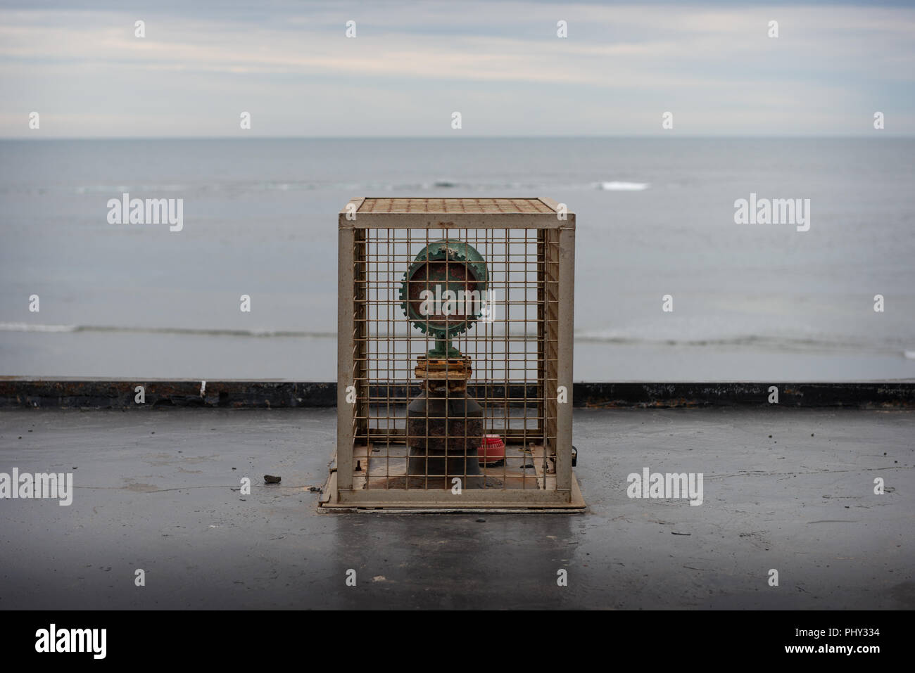 A caged object with ocean backdrop - Stock Image