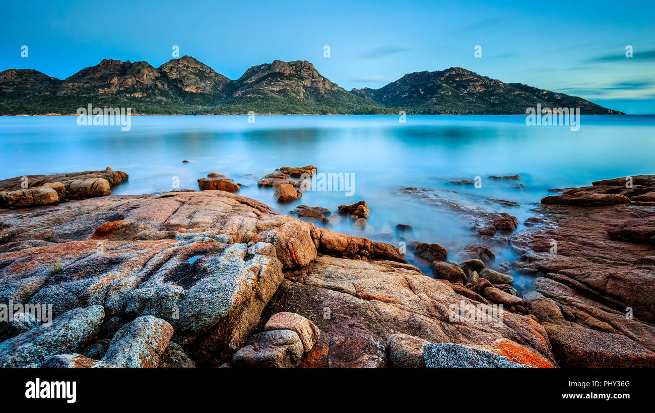 The Hazards in Freycinet National Park at dusk, viewed from Coles Bay in Tasmania, Australia, with orange lichen on granite rocks in the foreground. - Stock Image