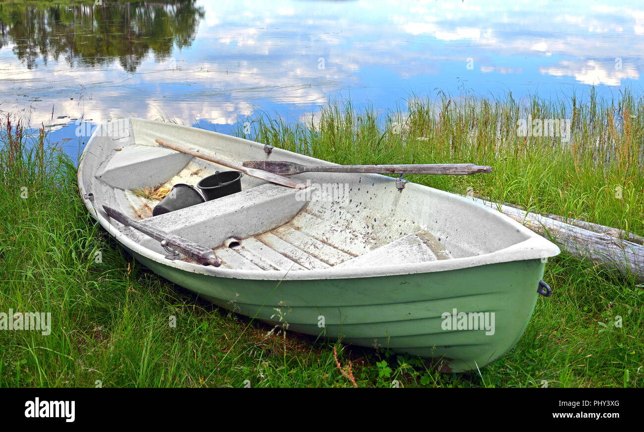 Old boat with oars on shore of lake. Finnish Lapland - Stock Image