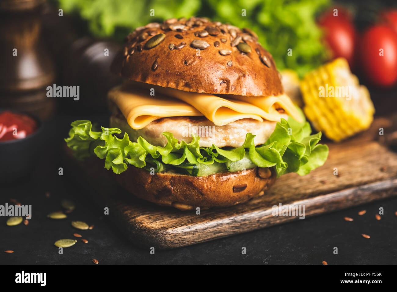 Chicken cheeseburger on whole grain bun with lettuce and grilled corn on wooden serving board. Closeup view - Stock Image