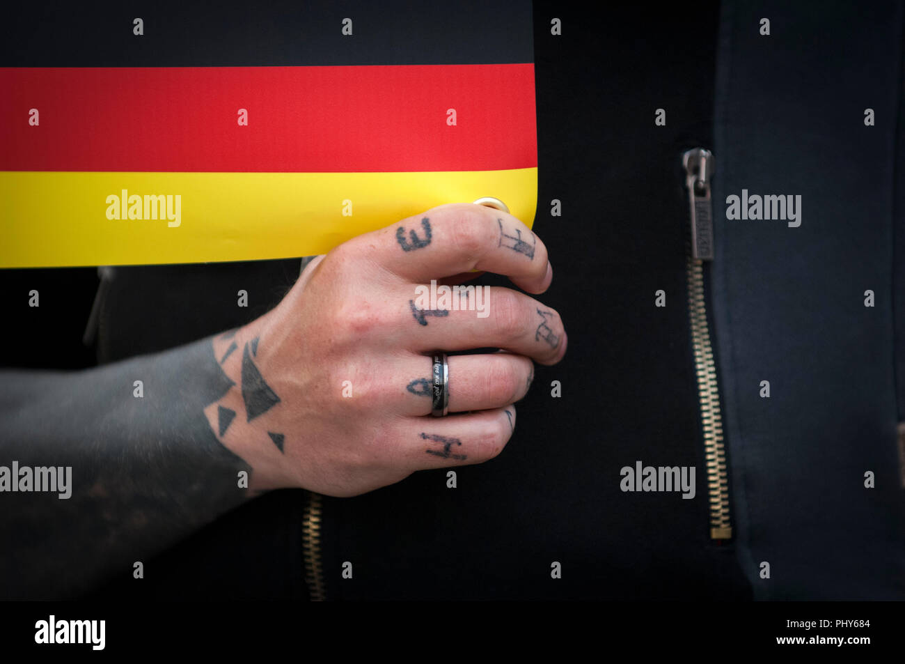 Far Right 'Pro Chemnitz' rally taking place at Gellerts Strasse outside the Chemnitz Football Club's. Demonstrator  has 'HATE 'tattooed on hand. - Stock Image