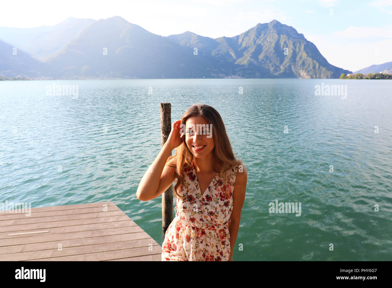 Portrait of happy beautiful woman on lake. Copy space. - Stock Image