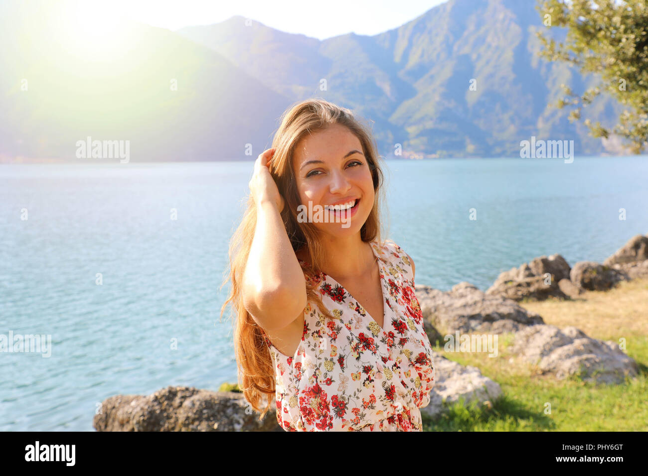 Portrait of happy beautiful woman on lake with flare sunlight - Stock Image