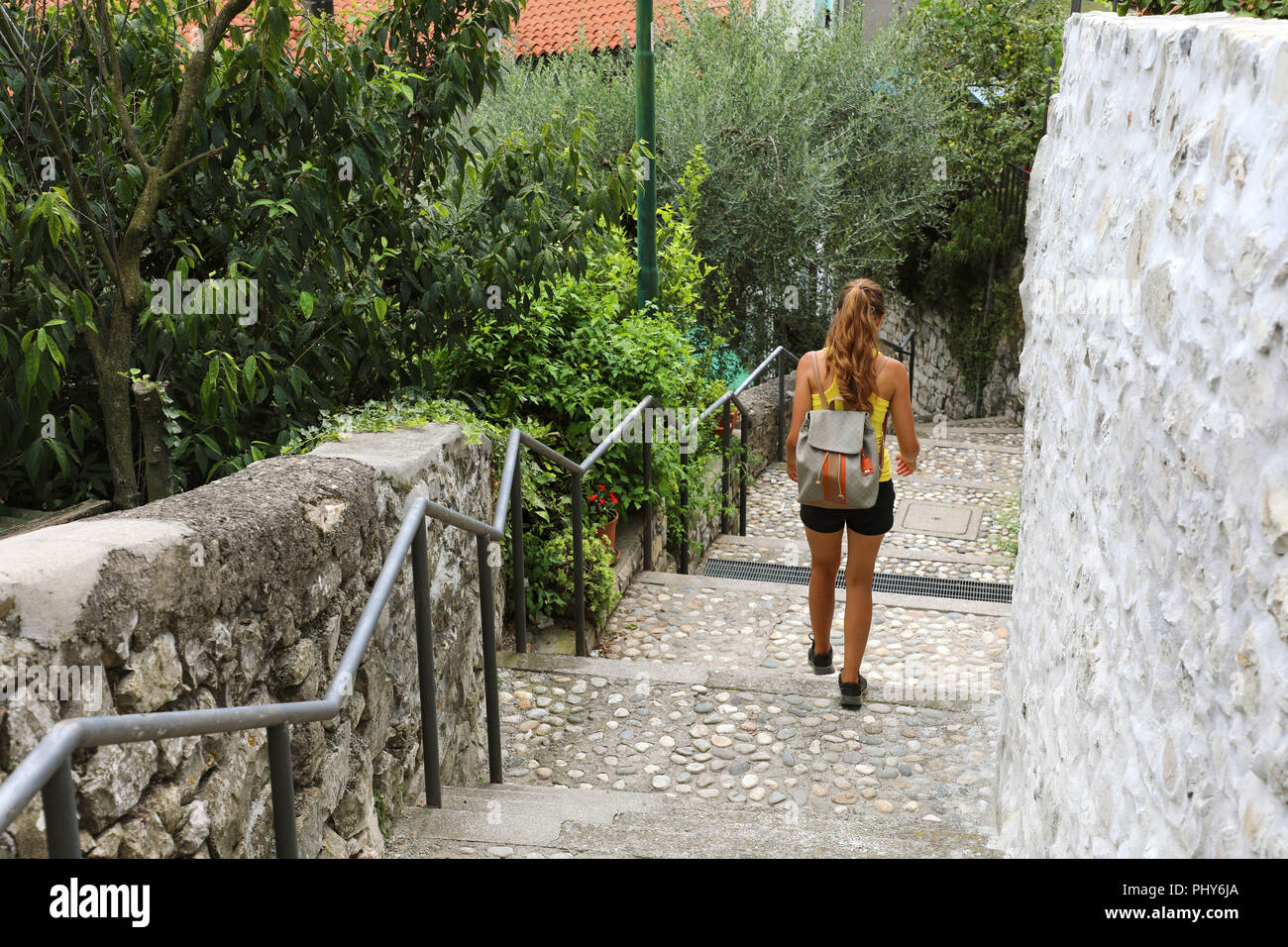 Female hiker go down and descent the stairs in Monte Isola, Italy - Stock Image