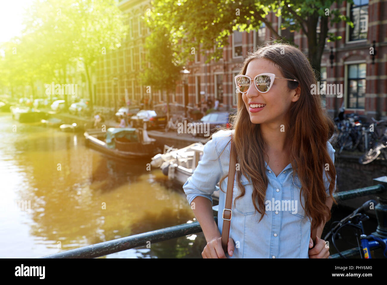 ed58330802081 Portrait of beautiful cheerful girl with sunglasses looking to the side on  one of typical Amsterdam channels