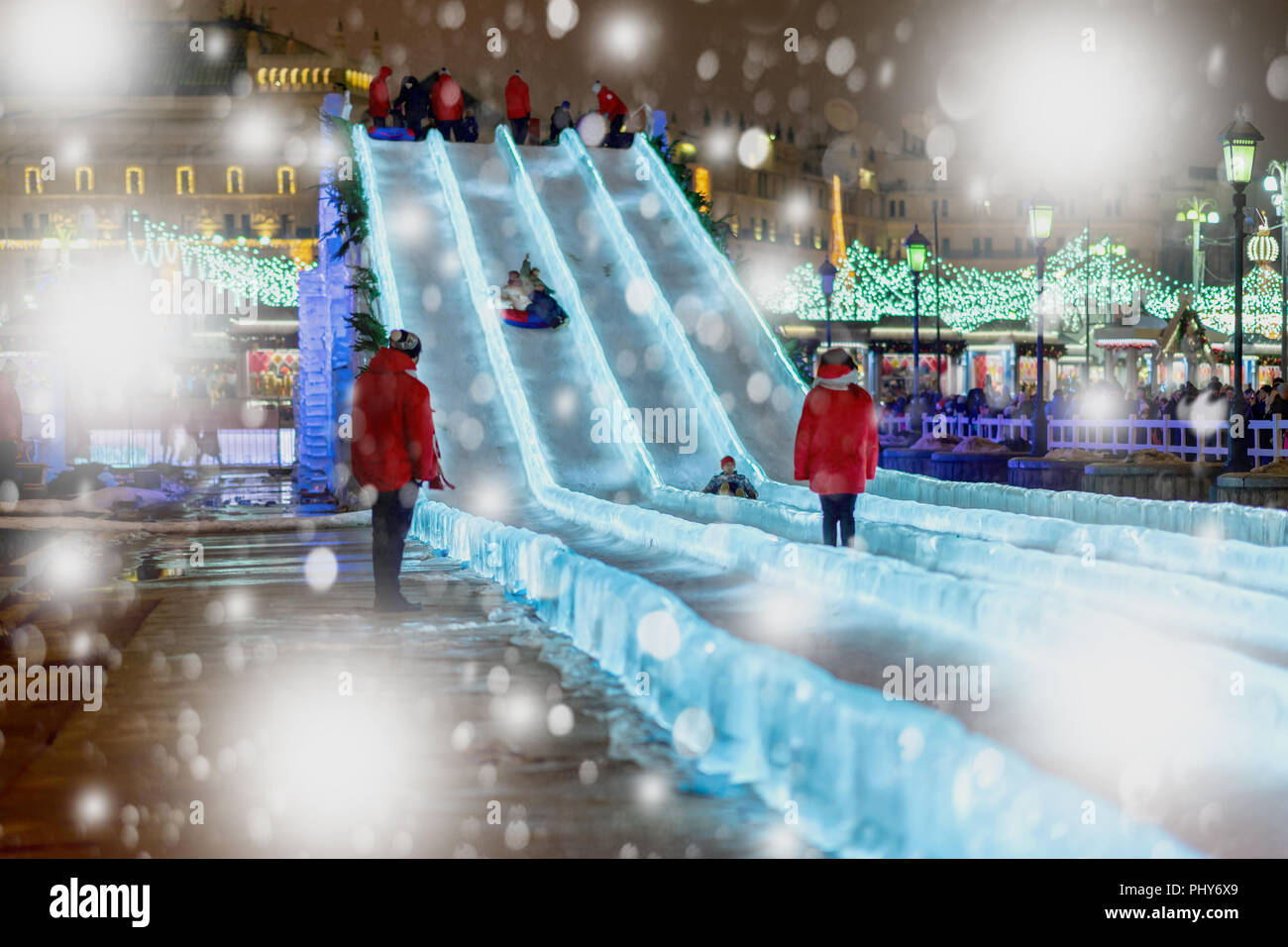 Abstract blurred background of Christmas street frozen hill , ice slide, fun leisure, skating, snowflakes - Stock Image