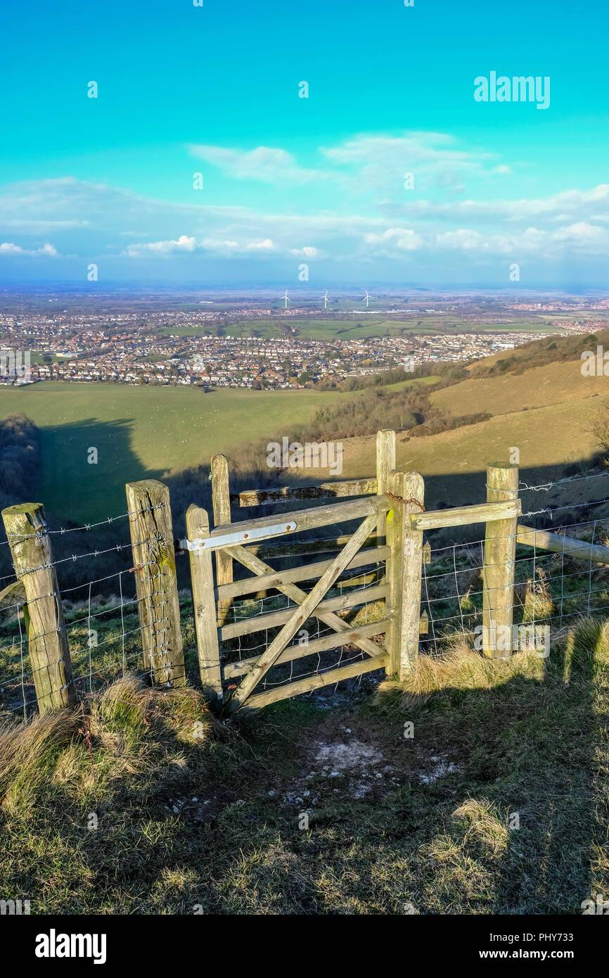 South Downs aerial view from the top  with a wooden gate in the foreground.  Looking down on Wannock, Polegate. Taken on a bright blue sky spring day. - Stock Image
