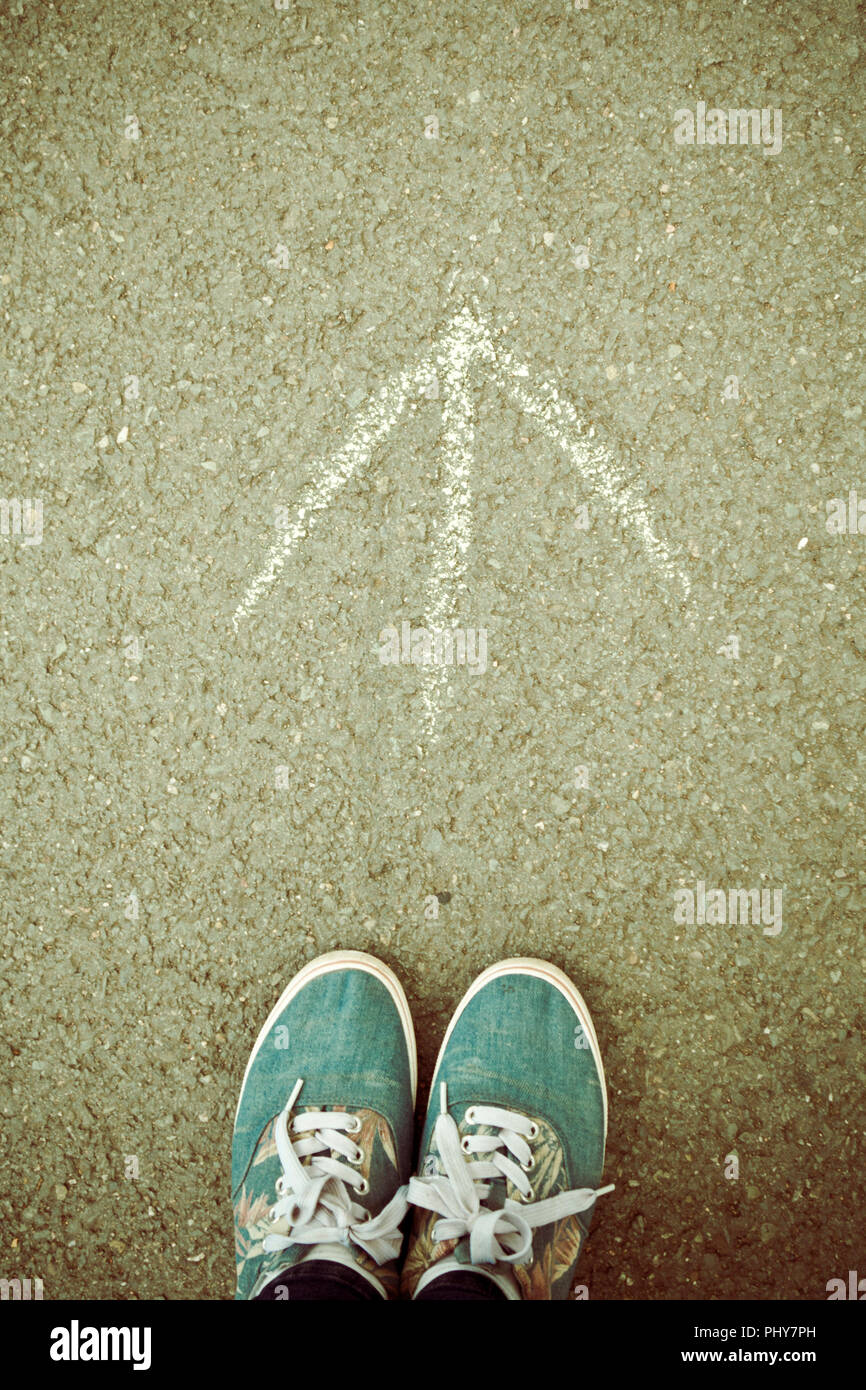 pair of shoes standing before an arrow drawn on the ground pointing forward, concept for success, future and moving forward - Stock Image