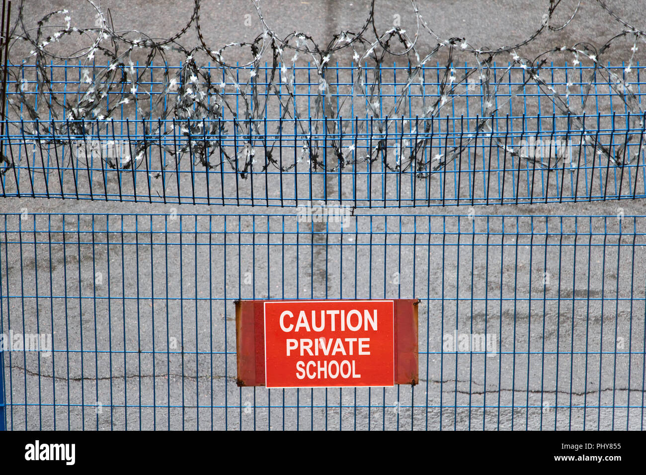 Iron fence with barbed wire. Metallic fence with red warning sign ...