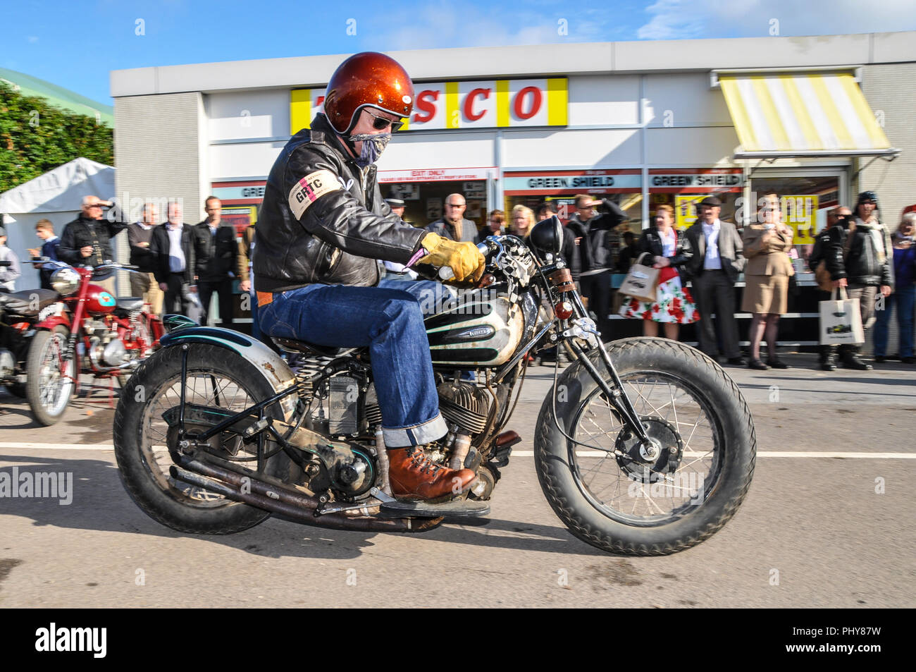 Period motorcyclist in retro leathers at the Goodwood Revival outside the retro Tesco shop, store. Vintage, classic, timeless. Step back in time - Stock Image