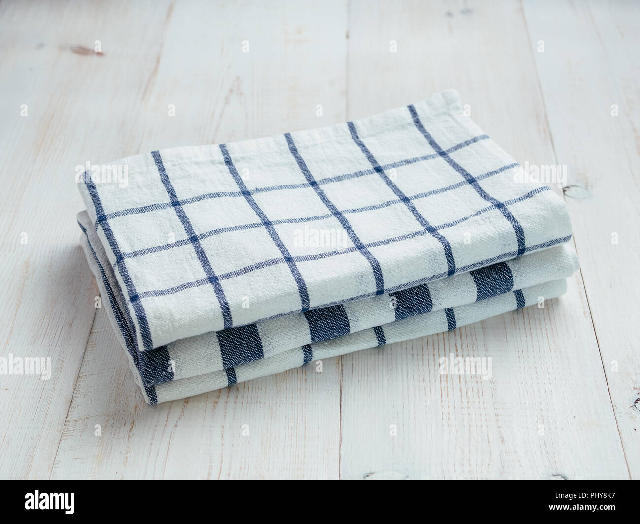 pile of white and blue kitchen linen towels. Stack of three ...
