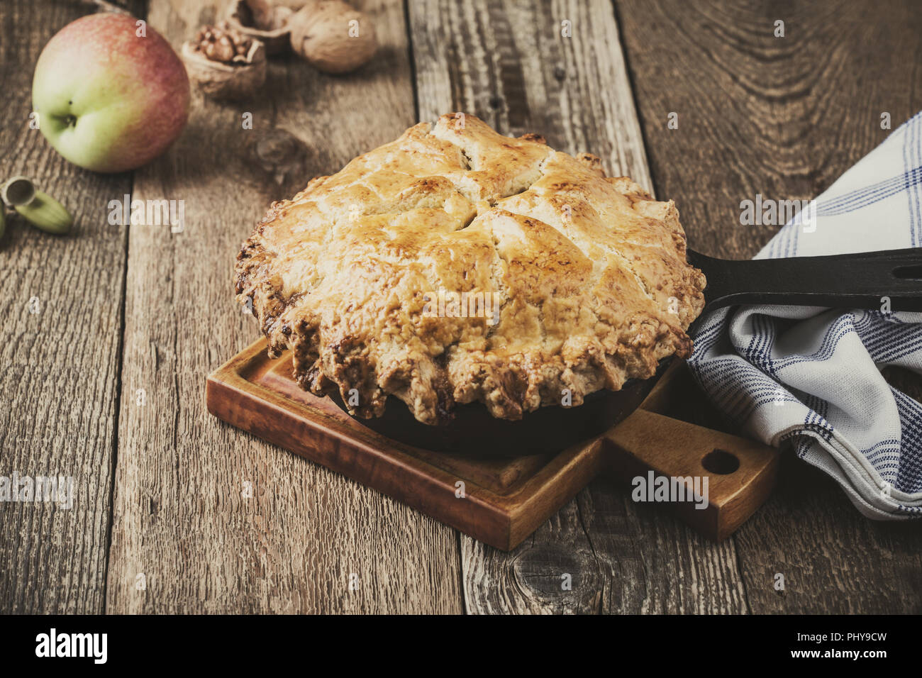 Apple pie in cast iron skillet on rustic wooden table, traditional autumn cozy dessert - Stock Image