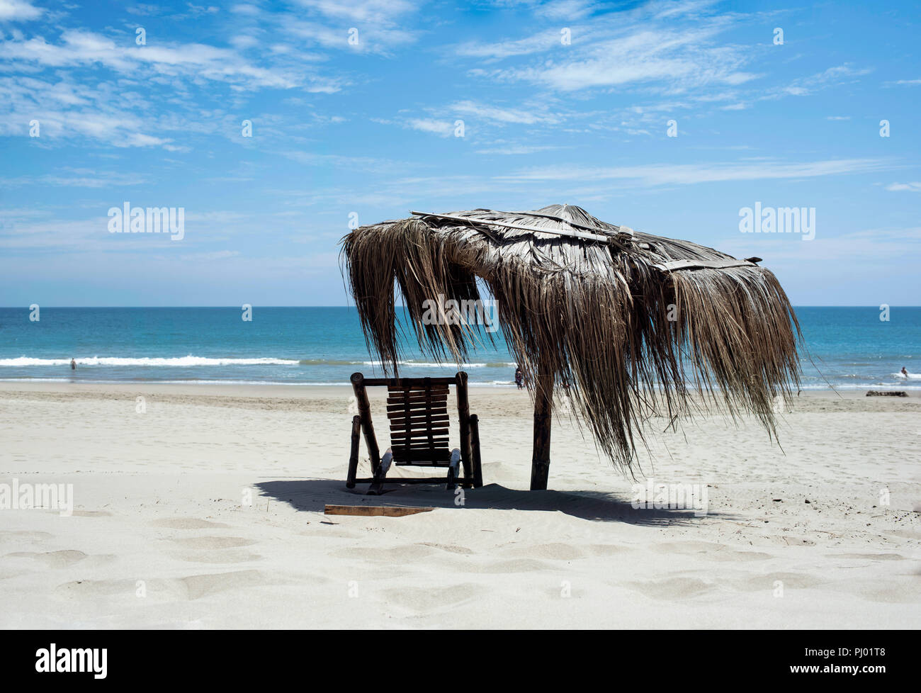 Rustic beach chair and straw umbrella with turquoise ocean view. Relaxed vibes on Vichayito beach near Mancora, Piura region, Peru. Aug 2018 - Stock Image