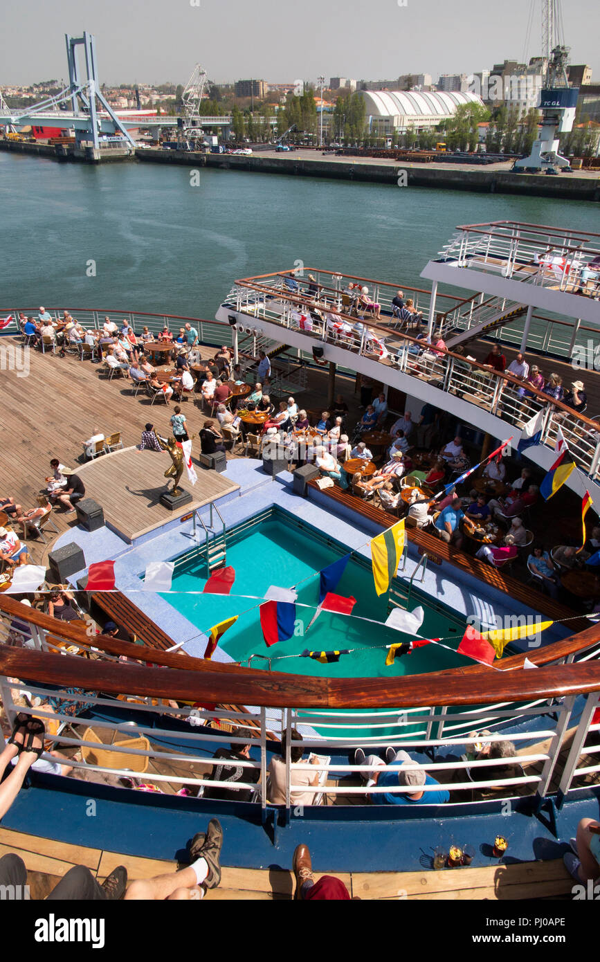 Portugal, Porto, Matosinhos, Leixoes Harbour, MV Marco Polo passengers on deck soround swimming pool in sunshine - Stock Image
