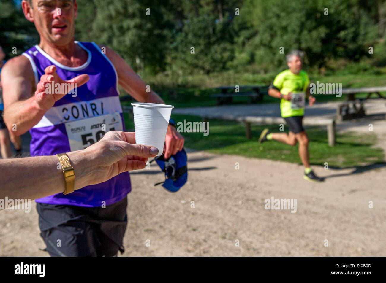 Runners grasping a plastic cup of water during 10k run. - Stock Image