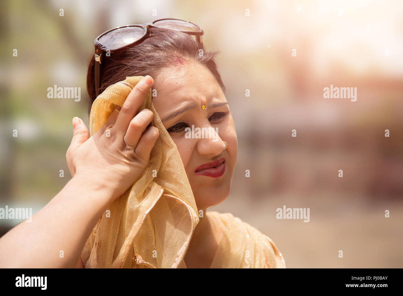 Woman shielding her eyes from sun. - Stock Image