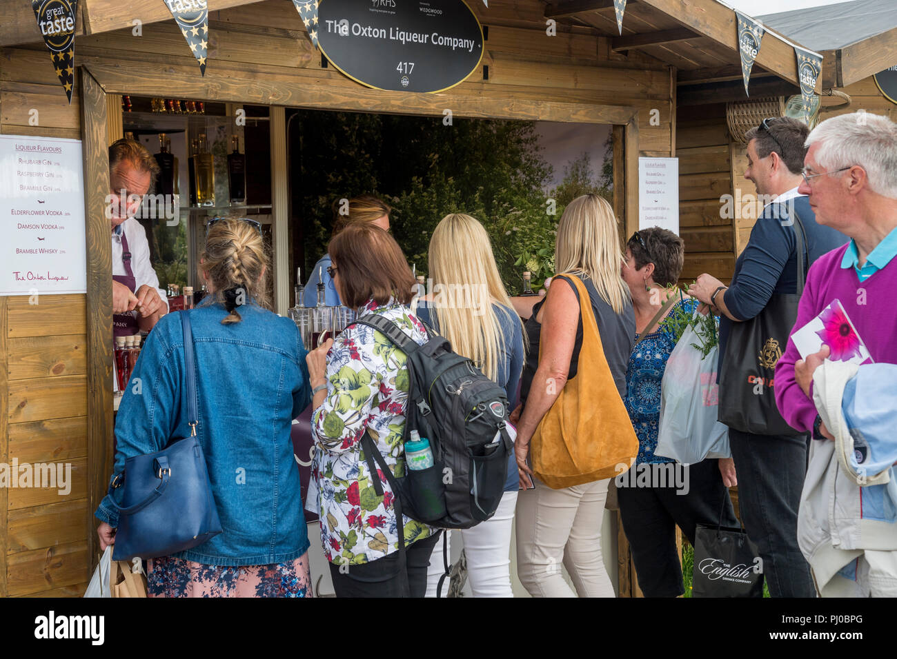 People being served, buying & queuing for handmade liqueurs in glass bottles at trade stand hut - RHS Chatsworth Flower Show, Derbyshire, England, UK. - Stock Image