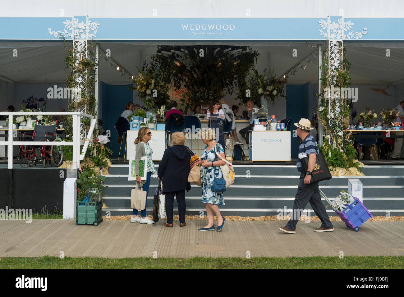 People at showground, walking past, standing by or sitting in Wedgewood refreshment marquee - RHS Chatsworth Flower Show, Derbyshire, England, UK. - Stock Image