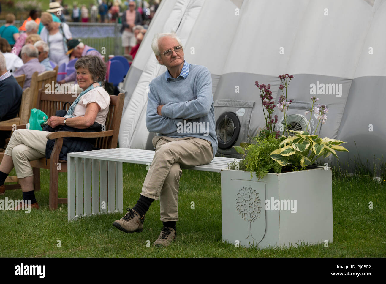 Senior man sitting alone on white bench seat, arms folded & legs crossed, crowd of people beyond - RHS Chatsworth Flower Show, Derbyshire, England, UK - Stock Image