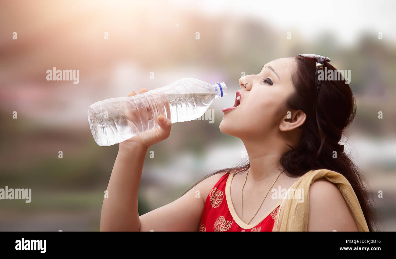 Beautiful Indian Woman drinking water from Bottle - Stock Image