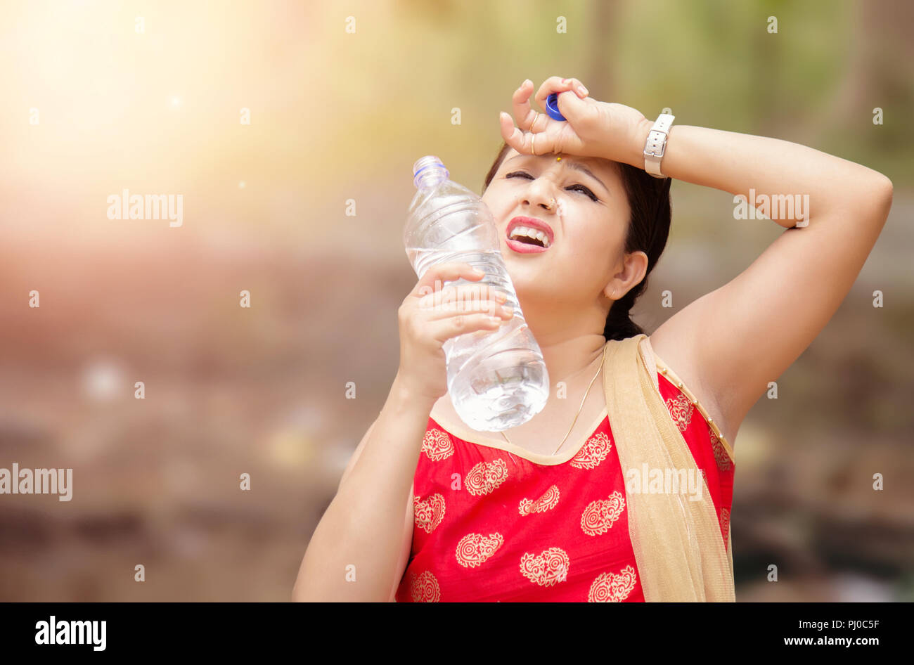 Young Indian woman holding water bottle during warm sunny day. - Stock Image