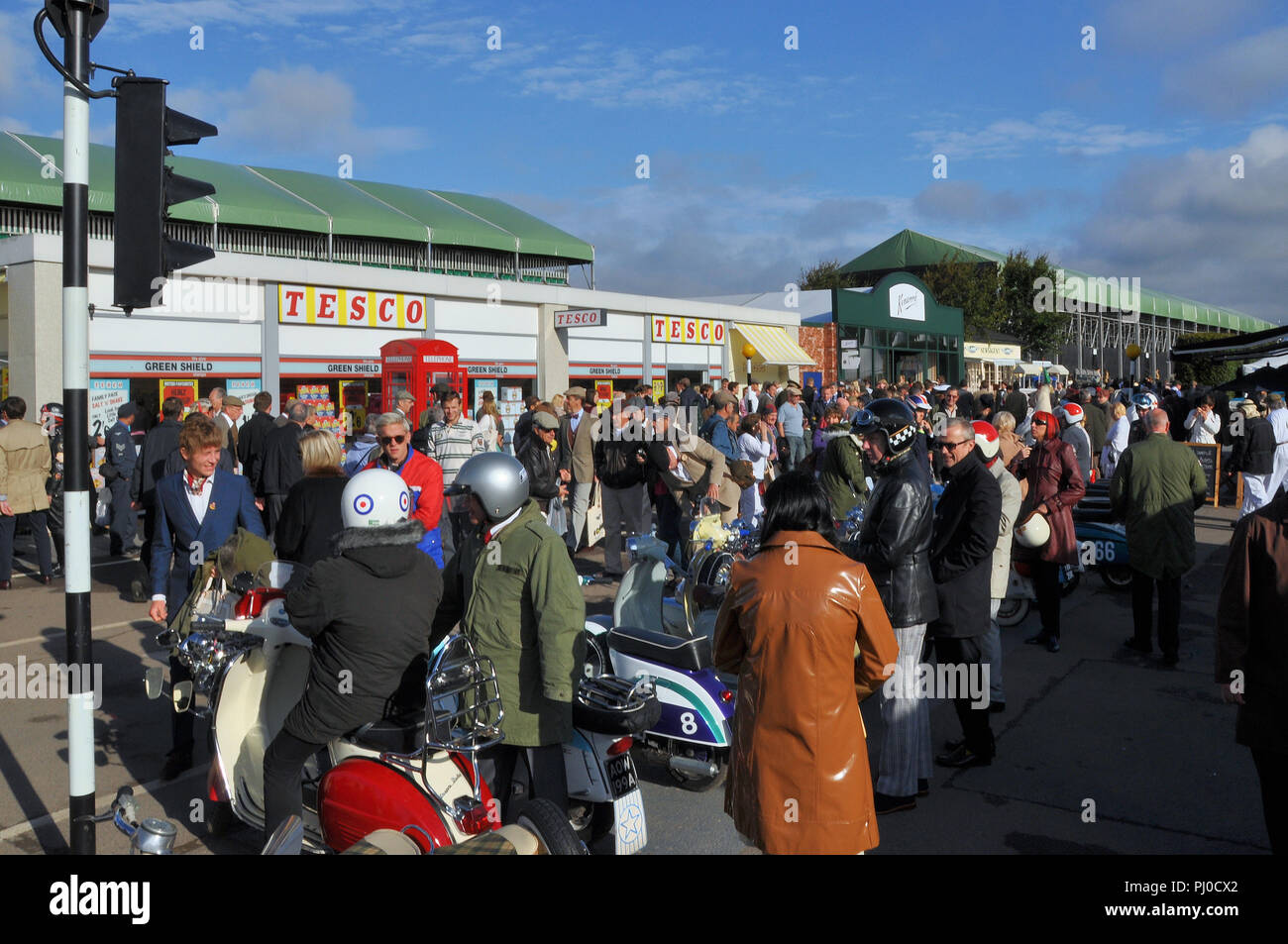 Street scene at the Goodwood Revival with people in period attire and mopeds. Retro Tesco store. Period costume. Timeless - Stock Image