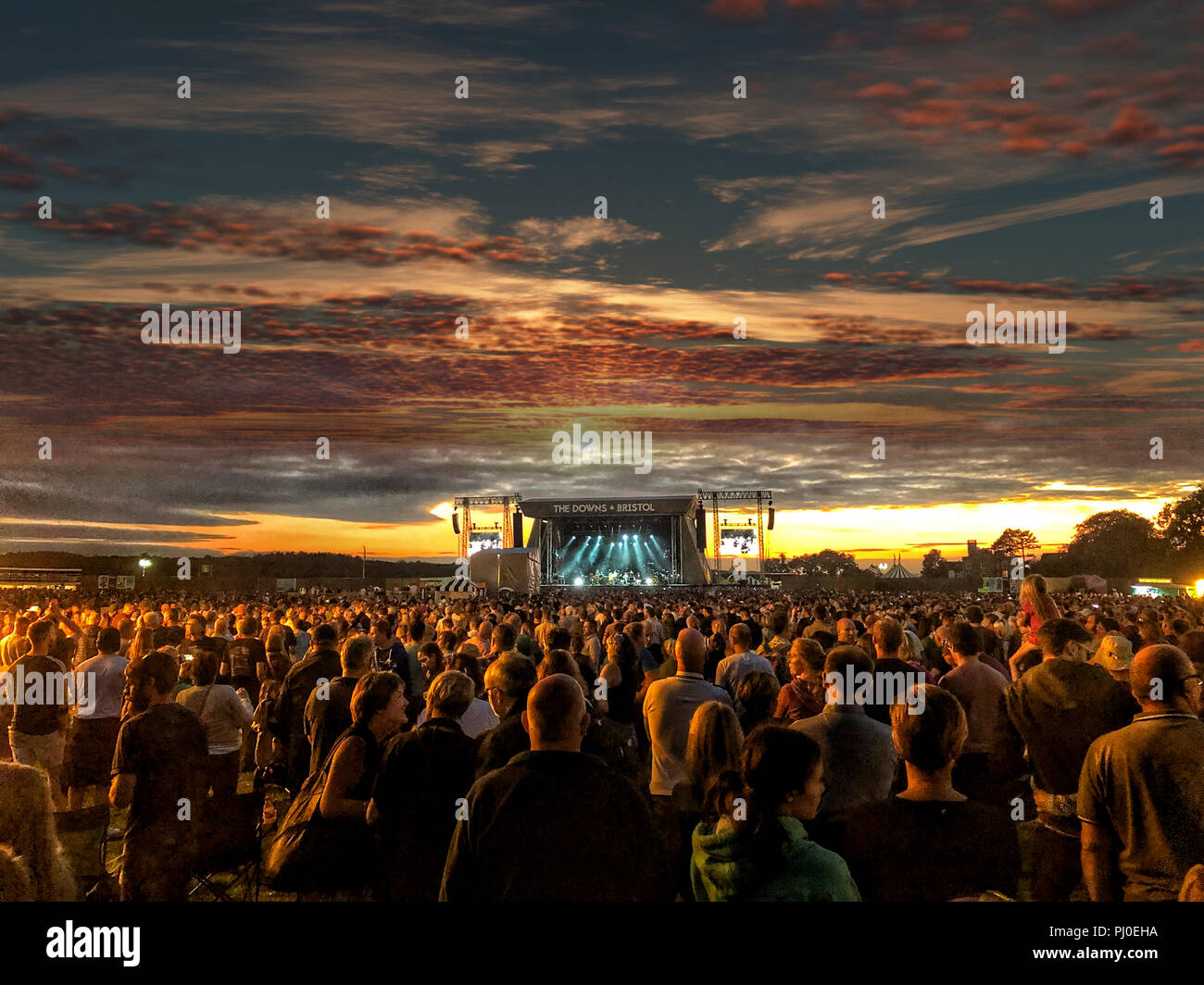 Large crowd watching music on a stage at sunset at a festival in Bristol ( The Downs ) summer vibes. - Stock Image