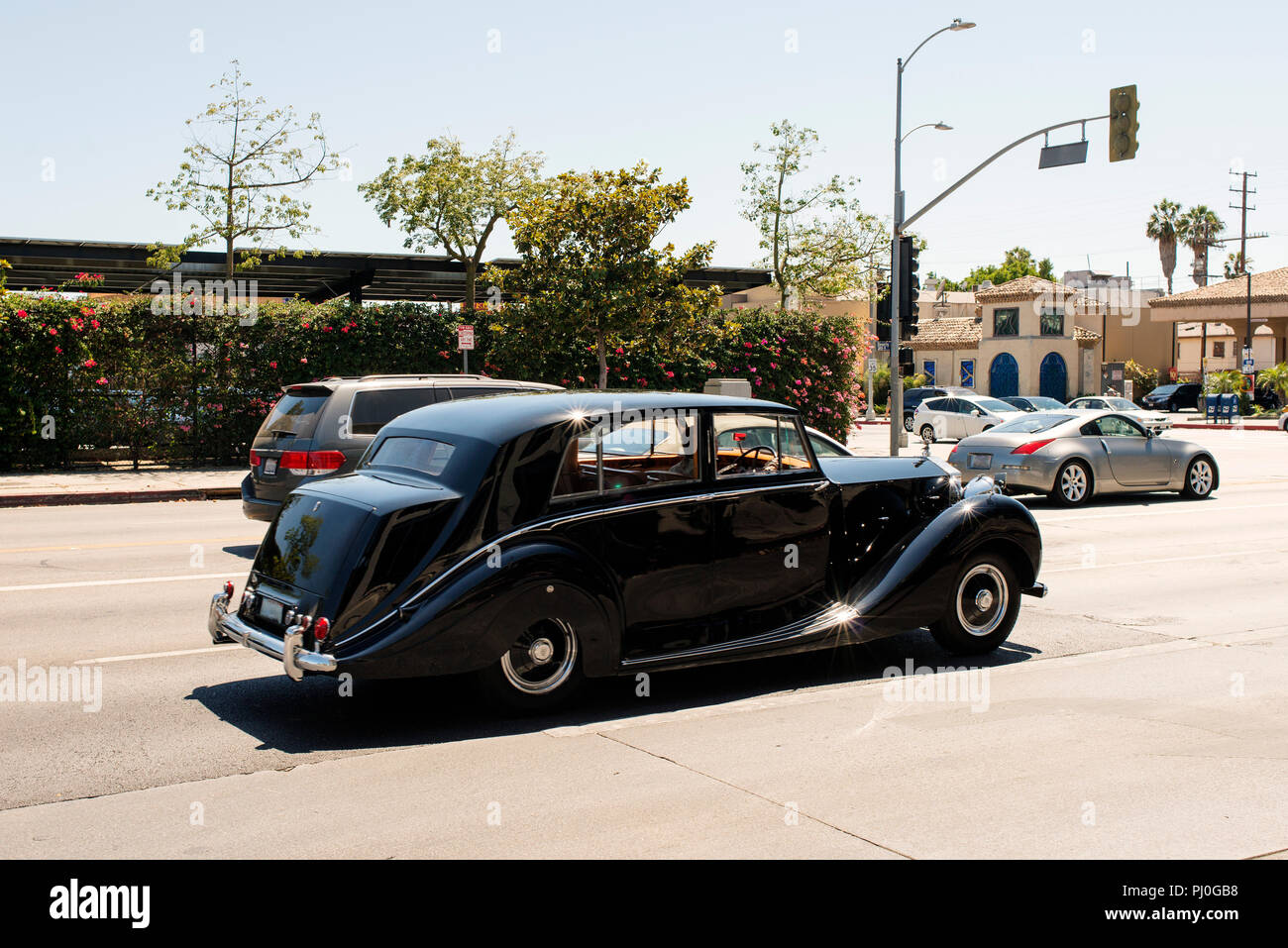 A view of an antique classic car passing by the street in West Hollywood, California in summer time - Stock Image