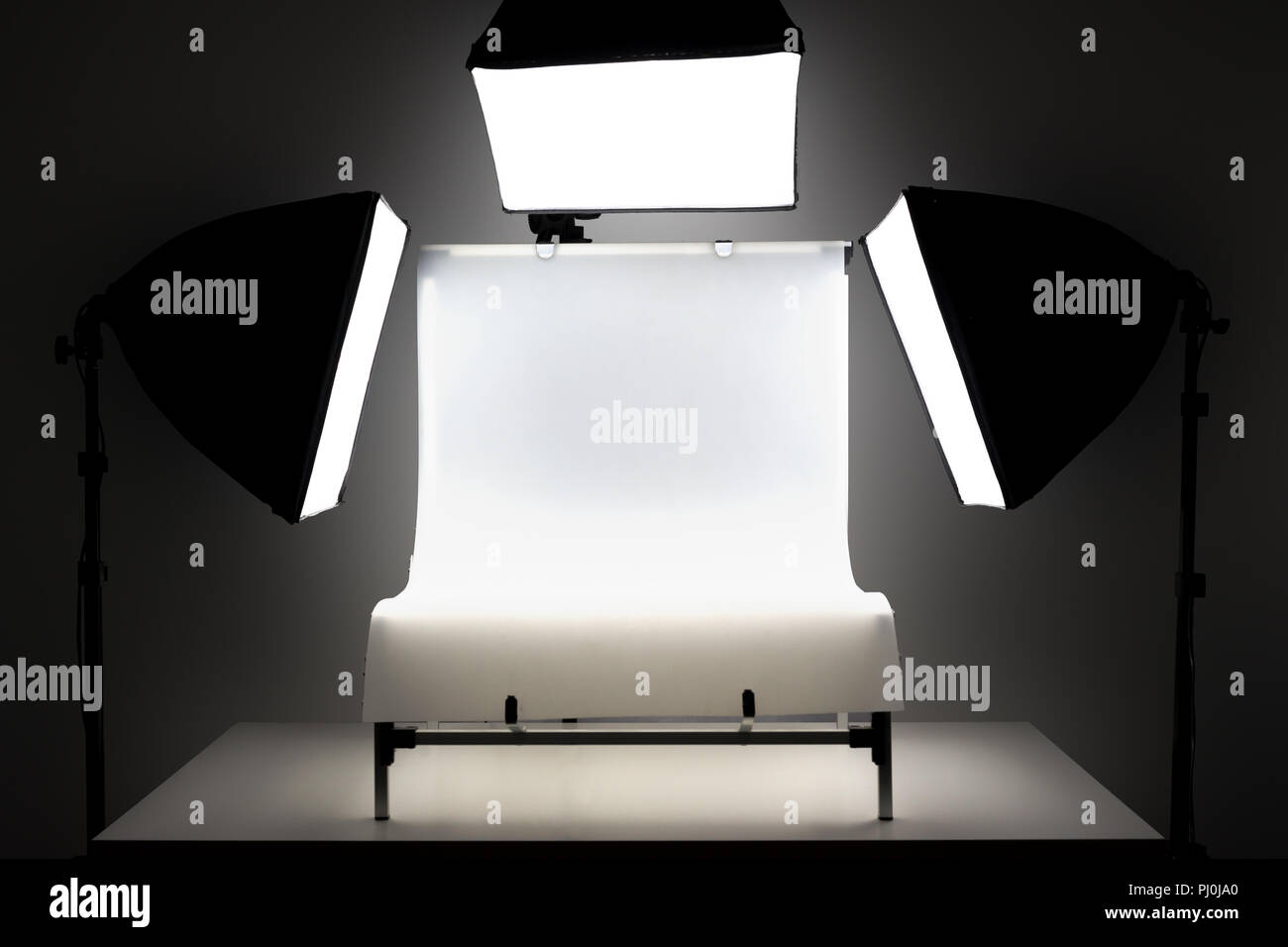 flashlights and shooting table photographic equipment on dark background - Stock Image
