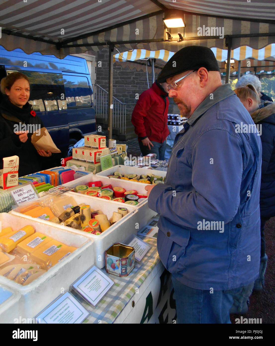 A customer looking to buy some local, and artisan, cheese at an open air food fair in New Lanark, Scotland. - Stock Image