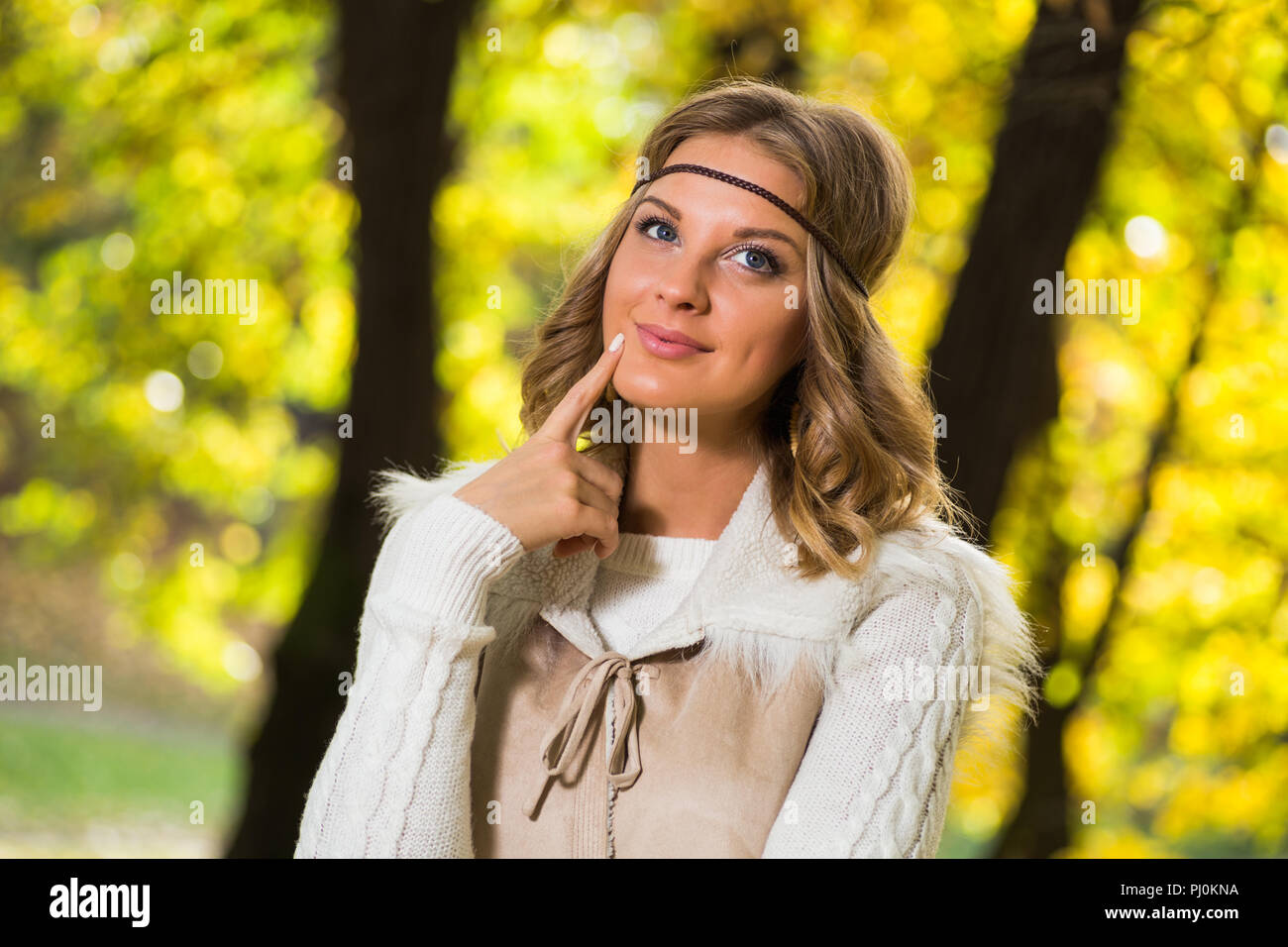 Beautiful boho girl enjoys in autumn day dreaming at the park. - Stock Image