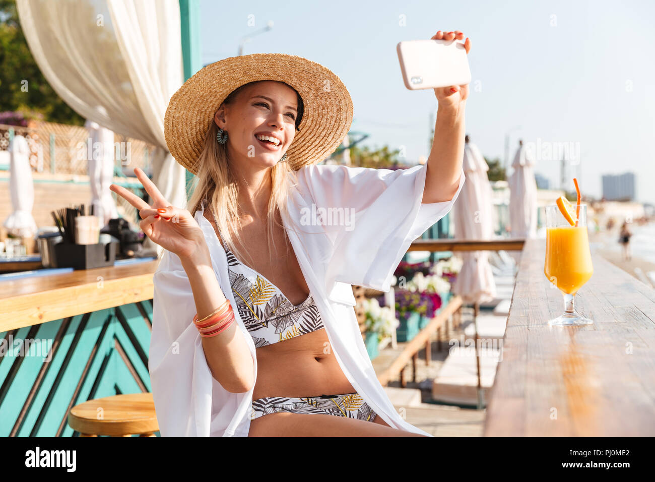 Photo of beautiful young woman 20s in straw hat and swimwear taking selfie on smartphone while drinking orange juice in beach bar during vacation Stock Photo