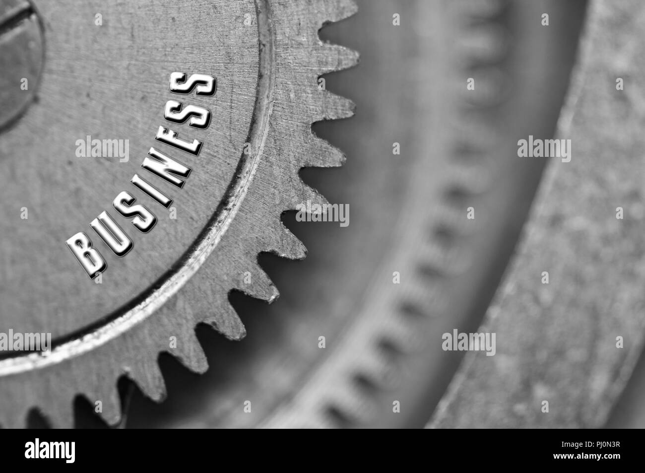 Background with the inscription BUSINESS. Black white background with metal cogwheels clockwork. Macro. Conceptual photo for your successful business  - Stock Image