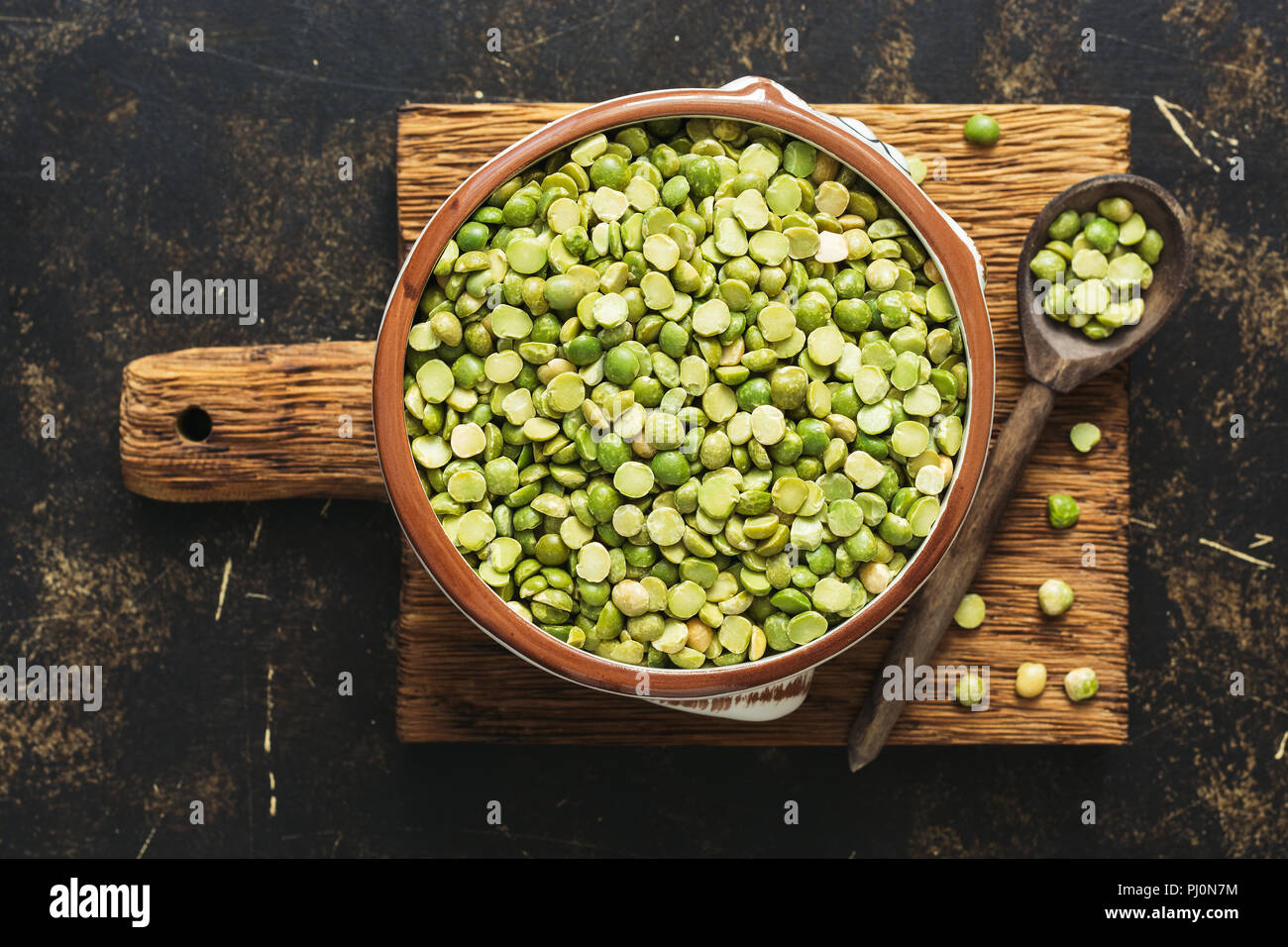 Green split peas in a bowl on a cutting board. Top view. - Stock Image