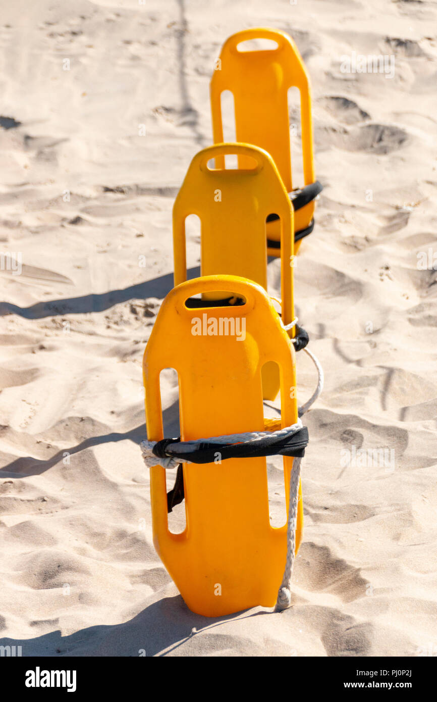 A close up view of three rescue can flotation devices in a row in the beach sand Stock Photo