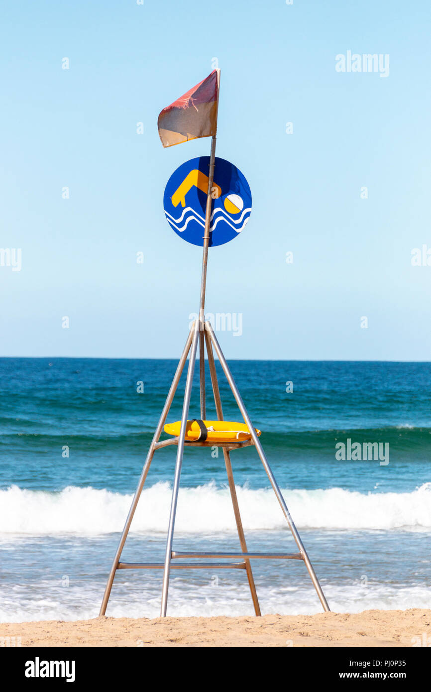 A close up view of a designated swimming area only sign on a metal stand on the beach with a resuce lifesavers can in the middle - Stock Image