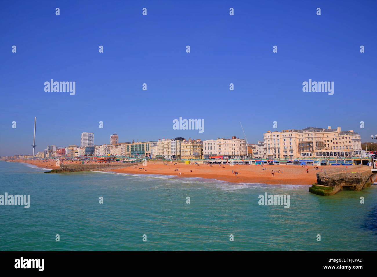 Brighton UK seafront and beach of popular south coast England uk tourist town with people - Stock Image