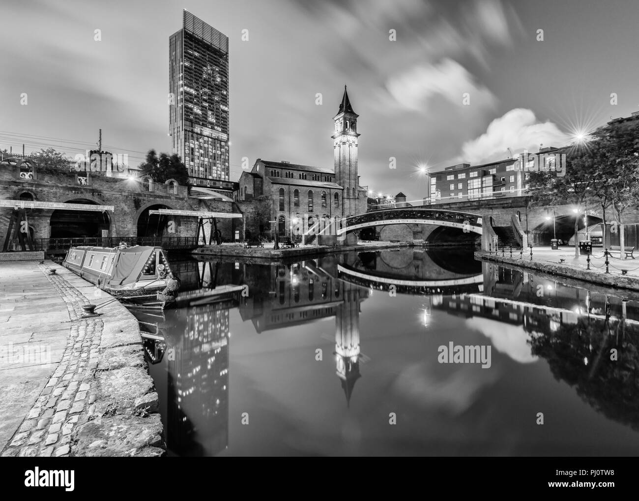 Black and white view from the Bridgewater canal towpath towards the old Congregational Chapel (now Pannone Corporate) and Hilton Hotel in Manchester - Stock Image