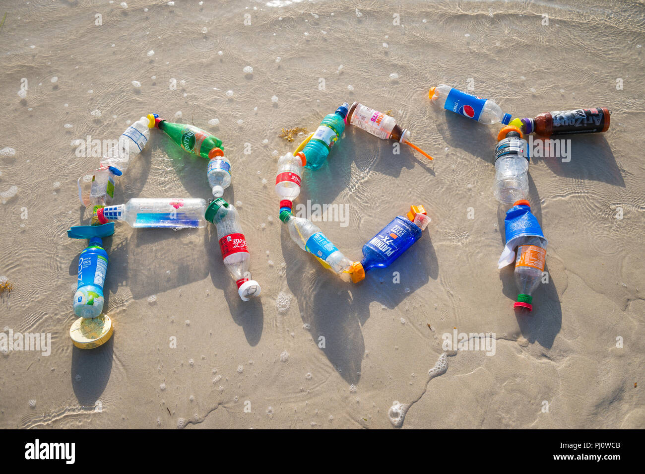 MIAMI - CIRCA JULY, 2018: 'Act' spelled out in the sand using garbage collected on Miami beach and in the sea. Reduce, reuse, recycle - Stock Image