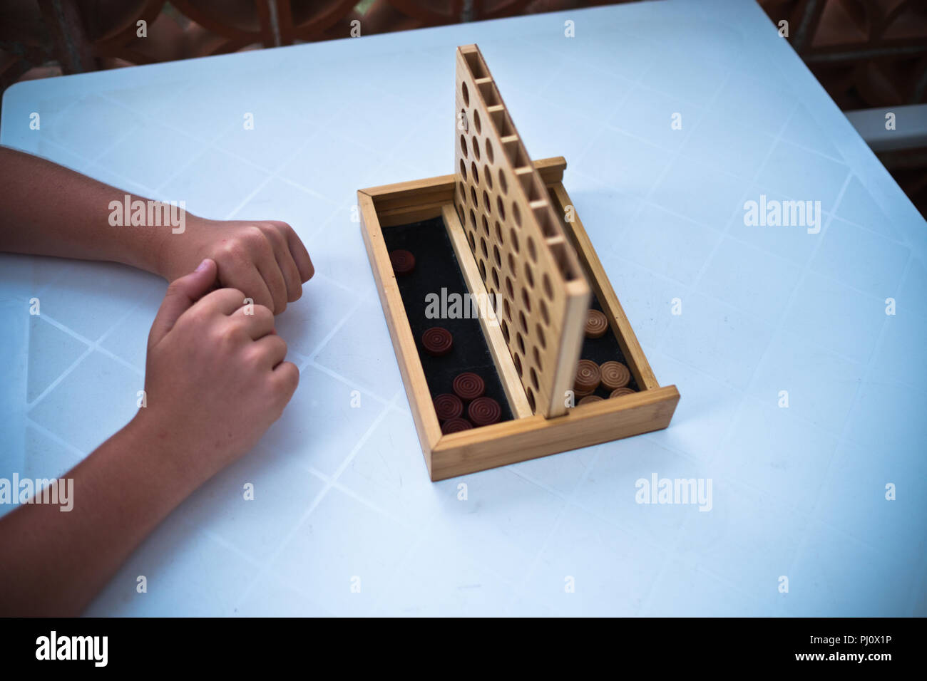 close up of bare arms with hands touching preparing to play game on wooden Connect four game on plastic white table on outdoor terrace in summer - Stock Image