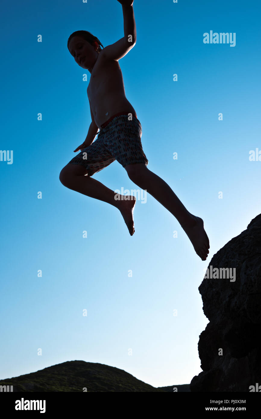 Low angle dynamic photograph of an eleven year old boy in swimming trunks leaping from a rock silhouetted against a blue sky, early evening - Stock Image
