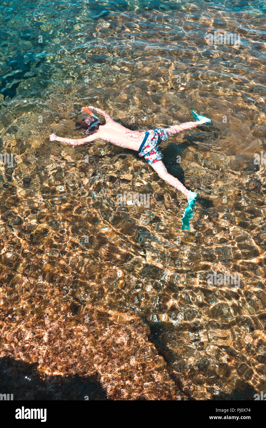 looking down onto an eleven year old boy snorkelling with his arms and legs spread eagled in clear crystal waters off Minorca, Spain - Stock Image