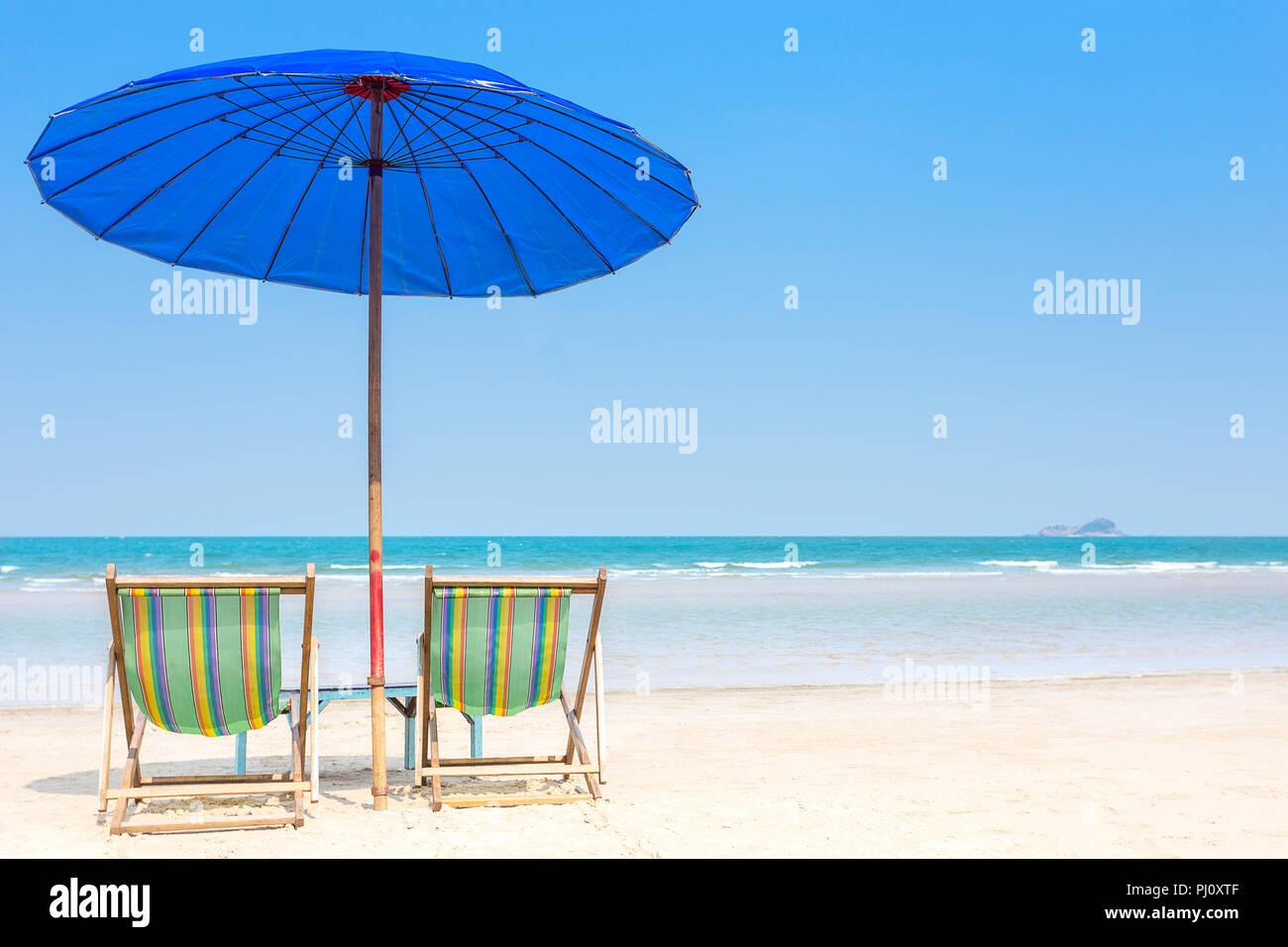 wood beach chair with blue umbrella on white sand beach with sea for