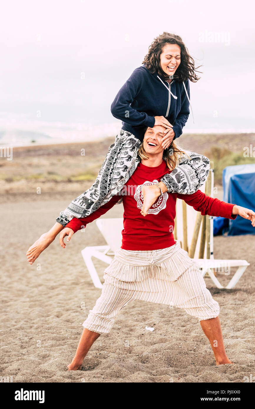 couple of caucasian young people man and female enjoy the summer beach. the man carry the female on his shoulder and both laugh like crazy while stay  - Stock Image