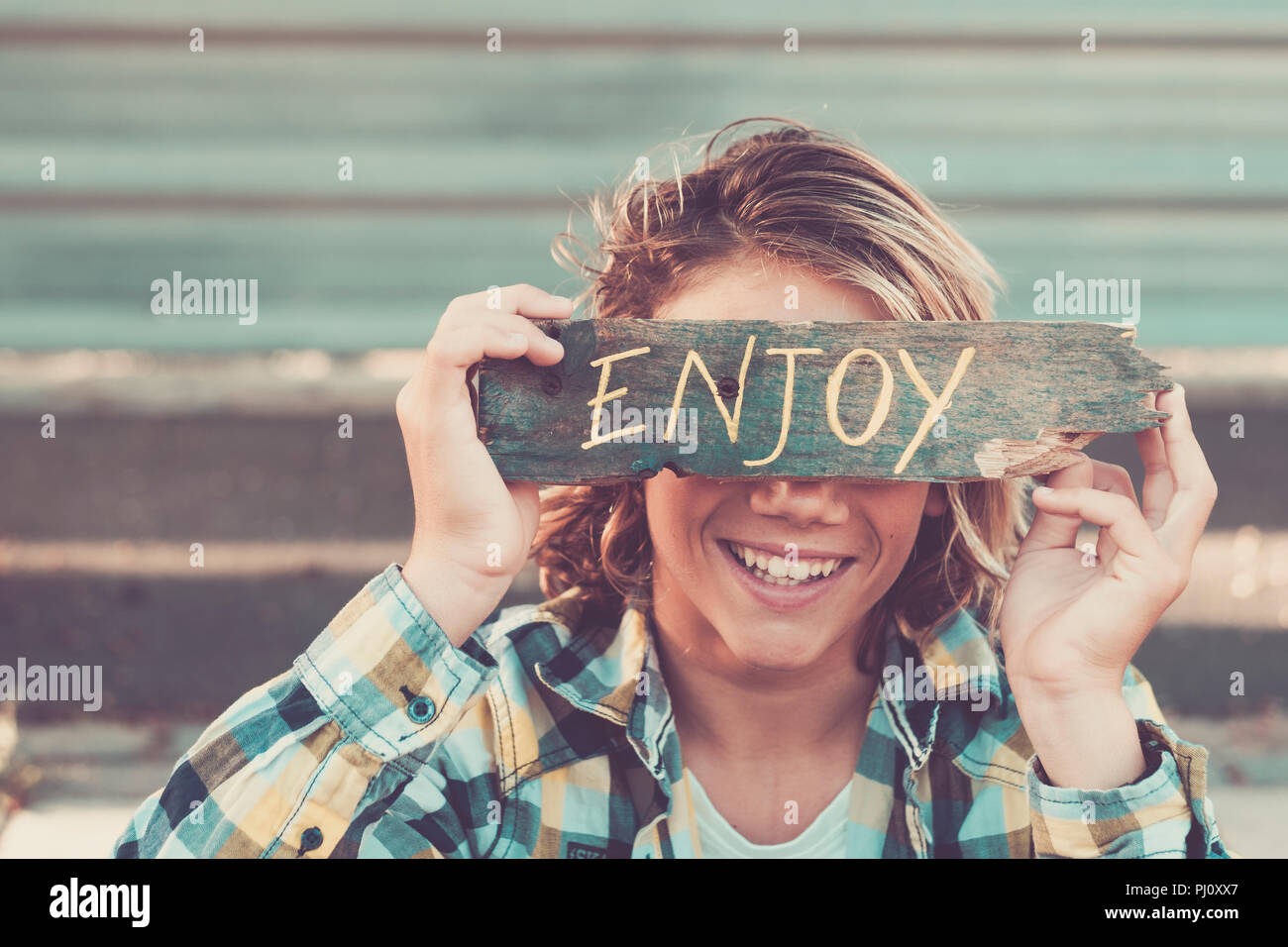 smiled young caucasian boy cover his beautiful face with a piece of wood written with enjoy message. urban background. vintage finlter picture for pos - Stock Image