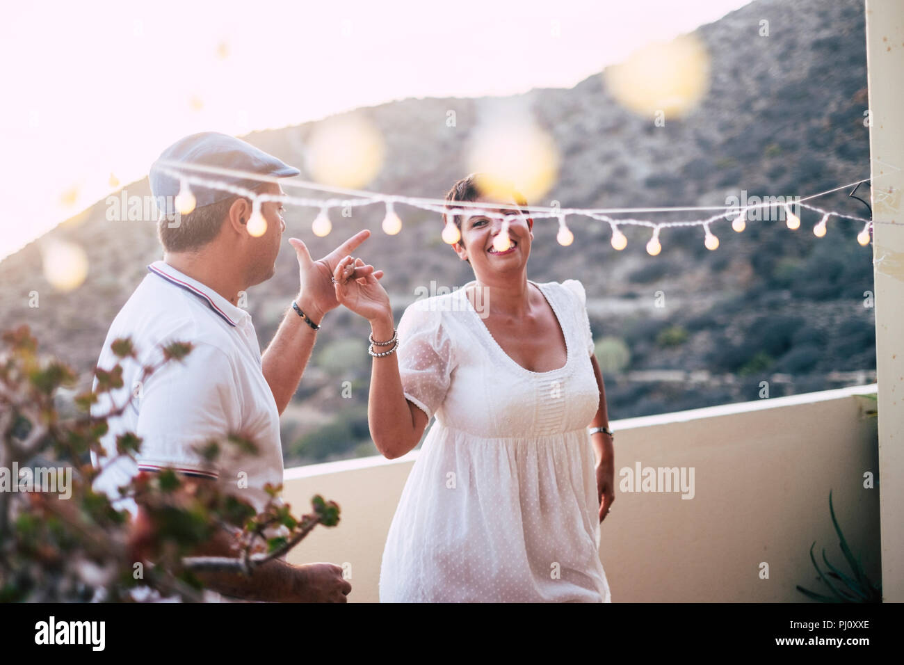 happy caucasian people dancing together at home in terrace with lights during the sunset. romantic and relationship concept image for happy people in  - Stock Image