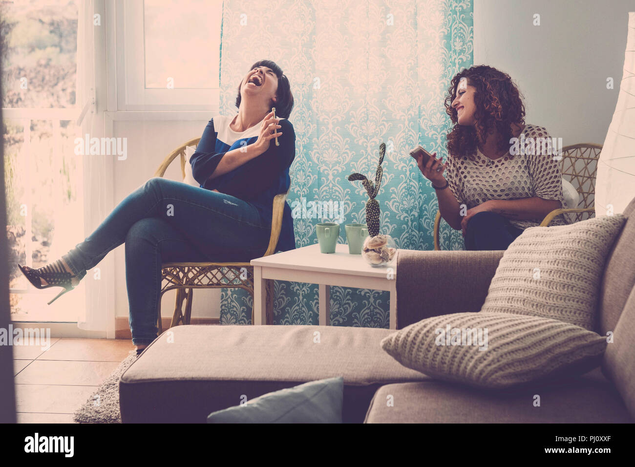 two young happy women friends sit down at home and laugh telling stories and facts about the day. indoor lifestyle concept in friendship with ladies u - Stock Image