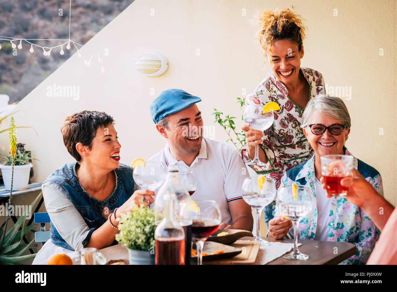group of adults mixed ages from 40 to 80 celebrate together at home in the terrace with food and wine. friendship together people concept having fun a - Stock Image