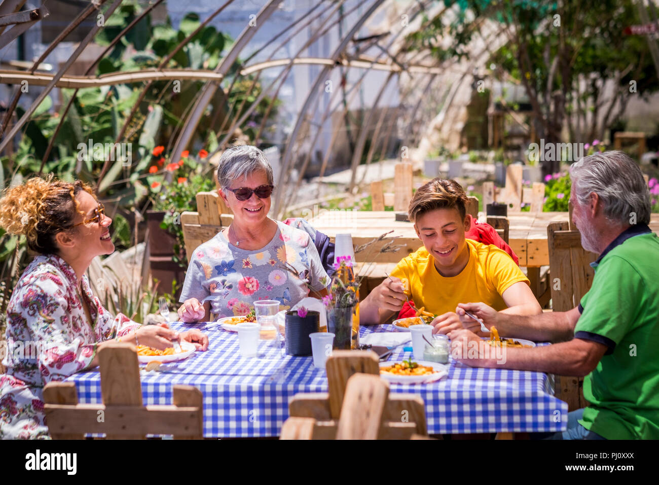 cheerful and happy family in alternative outdoor restaurant all natural and made with recycled wood pallets. nice caucasian people in leisure activity - Stock Image