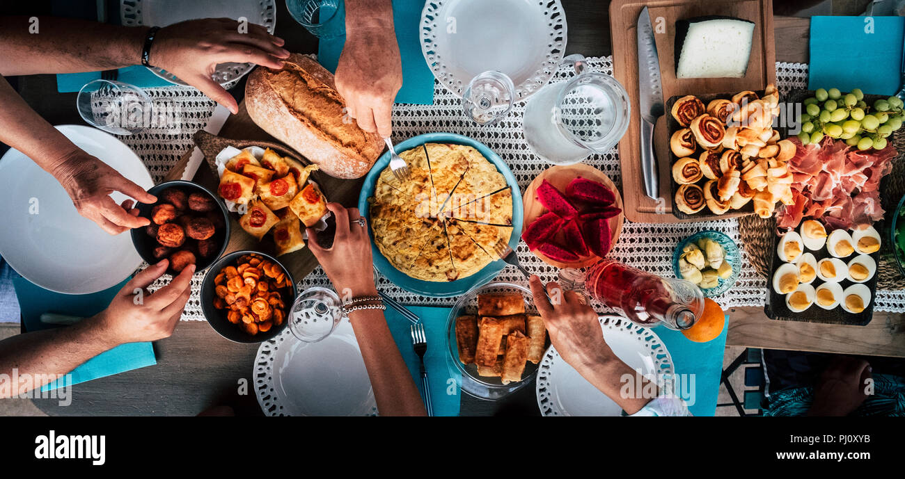 Food Catering Cuisine Culinary Gourmet Buffet Party Concept with lot of hands taking food from various mixed place on the table. having fu. community  - Stock Image
